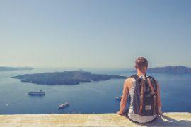 junger Backpacker sitzt am Meer